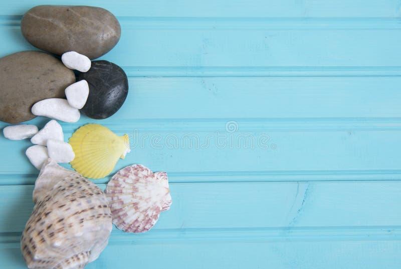 轻和黑暗的小卵石和多颜色壳的蓝色海滩背景图象 免版税库存照片