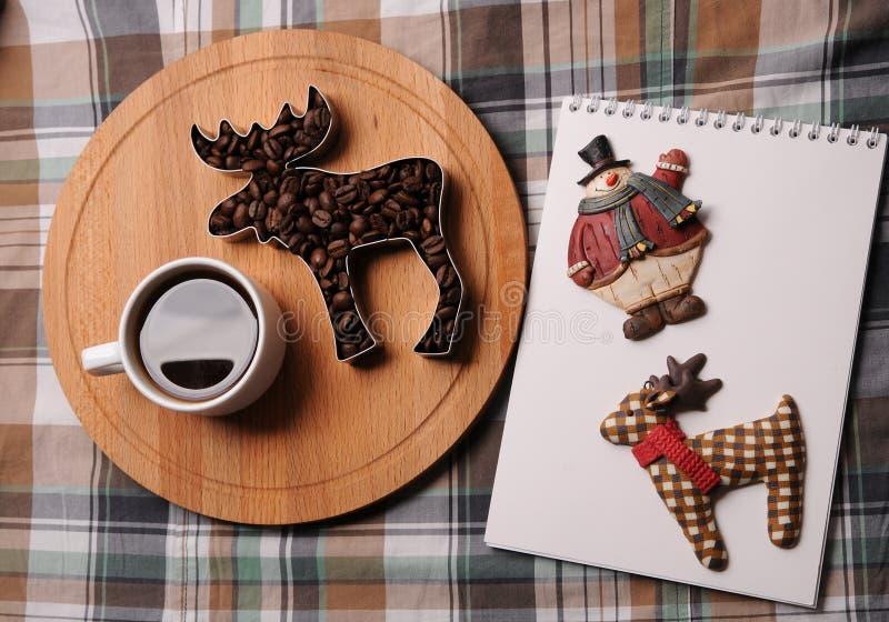 咖啡、咖啡豆以麋的形式在木板,笔记本有鹿的和雪人 在格子花呢披肩背景 库存照片