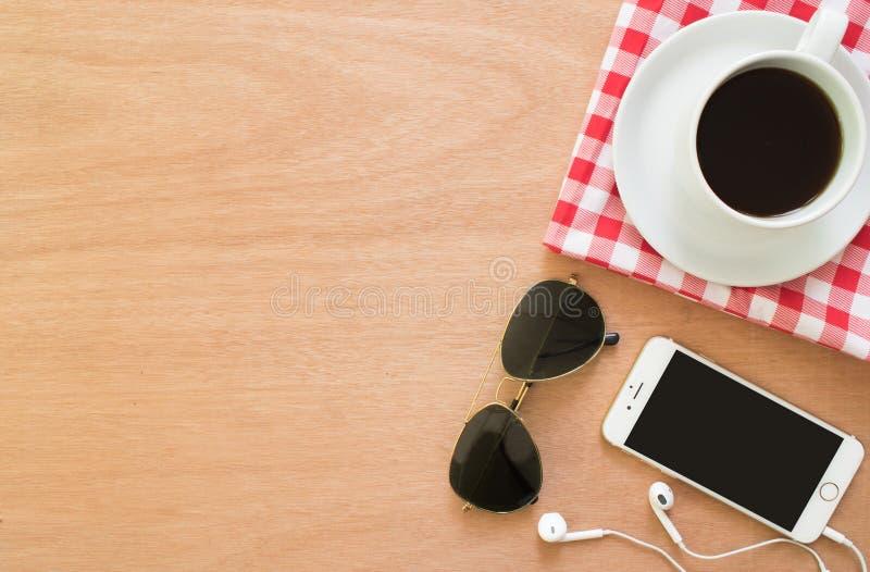 咖啡、布料红色格子花呢披肩、智能手机和玻璃在土气棕色木书桌上 生活方式工作区,顶视图 免版税库存照片
