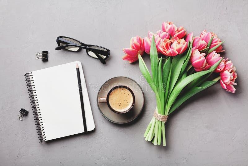 咖啡、干净的笔记本、镜片和美丽的郁金香在舱内甲板位置样式的石台式视图开花 妇女运转的书桌 库存照片