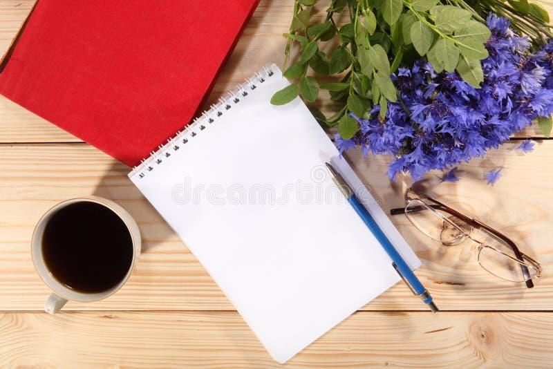 咖啡、开放笔记本、笔、眼镜和矢车菊 免版税库存照片