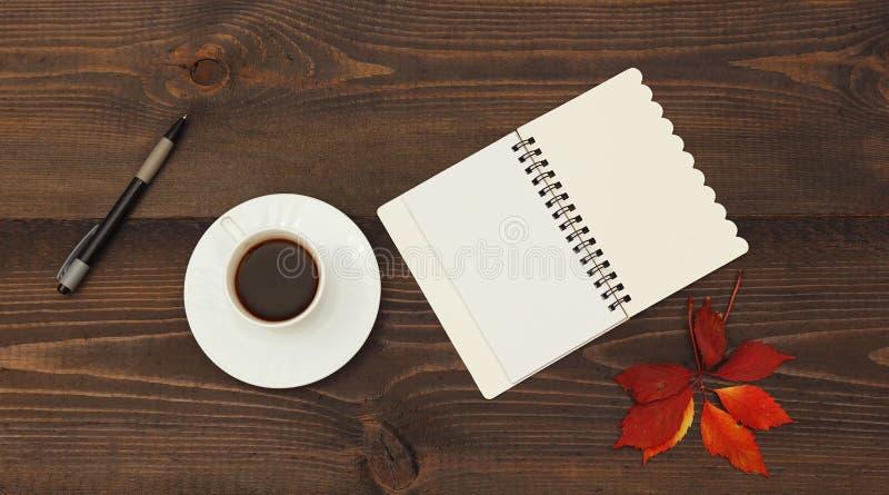 咖啡、开放笔记本、笔和秋天红色叶子在木桌上 在视图之上 图库摄影