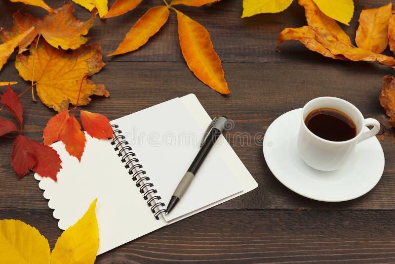 咖啡、开放笔记本和笔在秋叶中在木背景 免版税库存照片