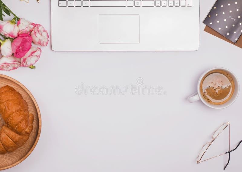 咖啡、新月形面包在盘子,花和小辅助部件在白色桌,顶视图上 库存照片