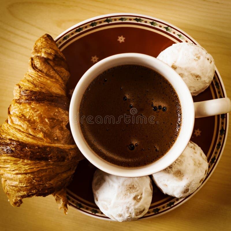 咖啡、曲奇饼、一个新月形面包和圣诞节开花 免版税库存图片