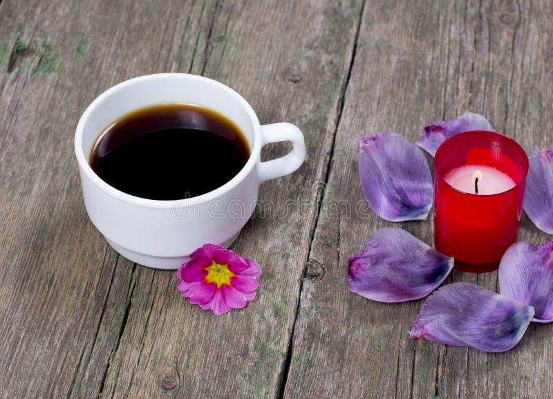 咖啡、淡紫色瓣和红色蜡烛,在一张木桌上 库存照片