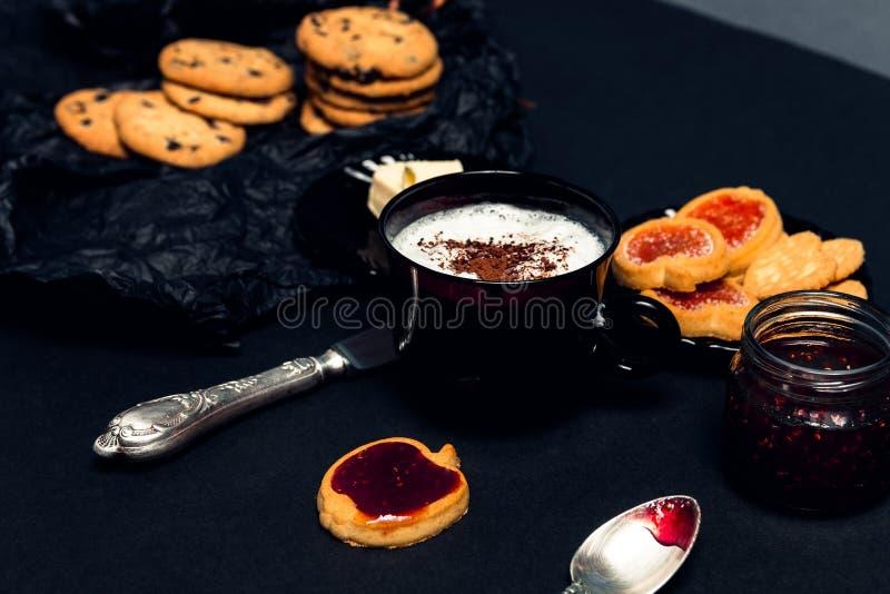 咖啡、热奶咖啡用巧克力曲奇饼和饼干在黑桌背景 下午断裂时间 早餐 免版税库存照片