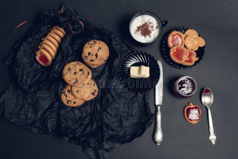 咖啡、热奶咖啡用巧克力曲奇饼和饼干在黑桌背景 下午断裂时间 早餐顶视图 免版税库存照片