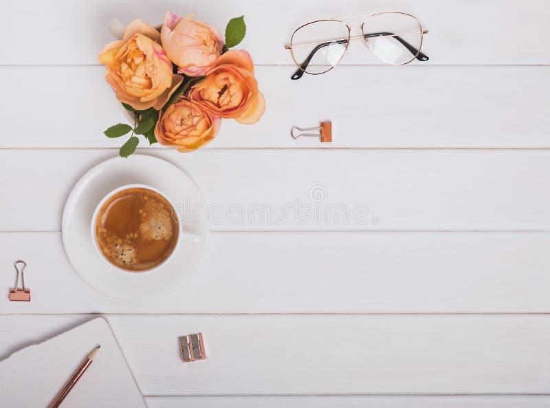 咖啡、玫瑰和其他项目在白色木背景,顶视图 库存图片