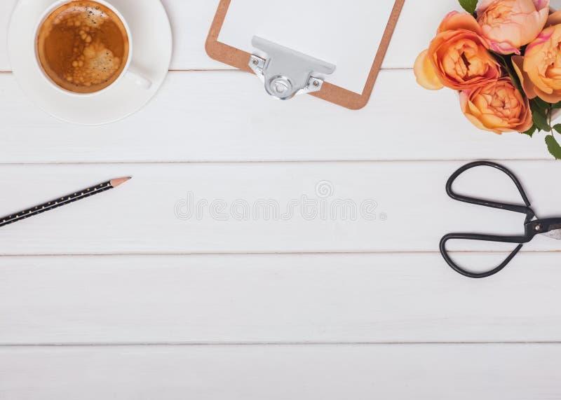 咖啡、玫瑰和其他项目在白色木背景,顶视图 库存照片