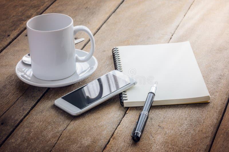 咖啡、笔记本、笔和巧妙的电话 库存照片