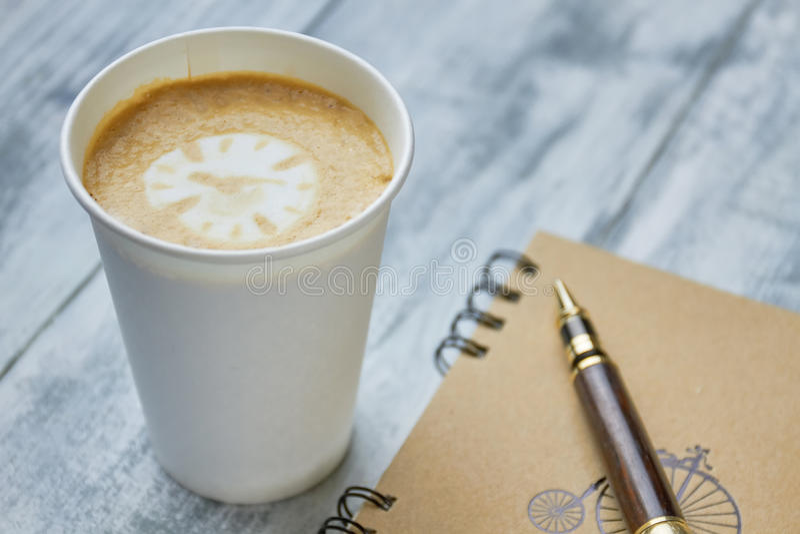咖啡、笔记本和笔 免版税库存照片