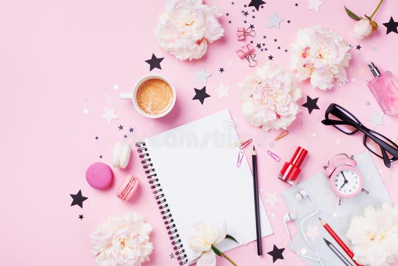 咖啡、蛋白杏仁饼干、闹钟、办公用品、牡丹花和笔记本在桃红色淡色台式视图 r 免版税库存照片