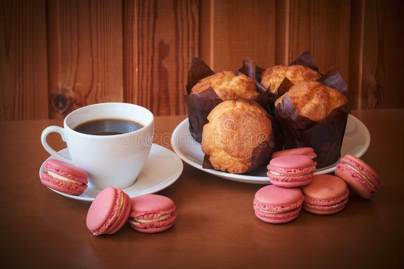 咖啡、蛋白杏仁饼干和松饼在木桌上 选择聚焦 免版税库存照片