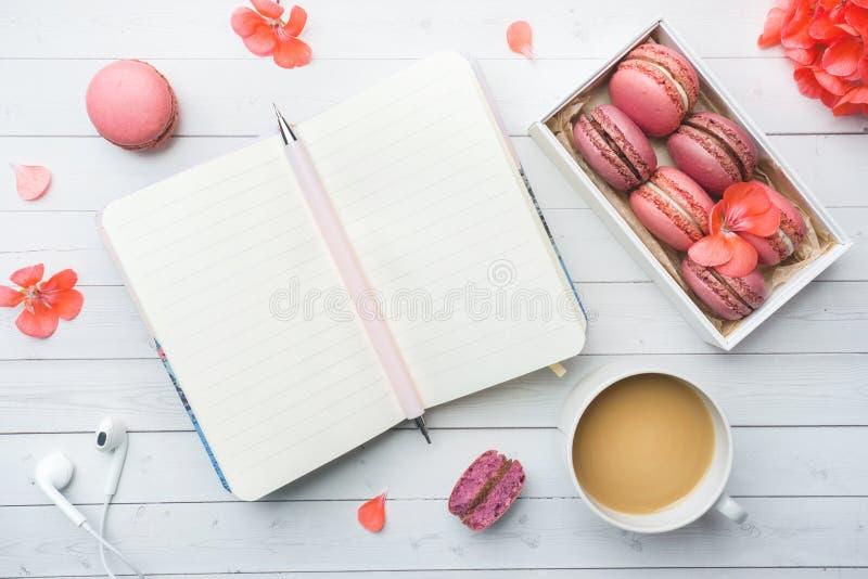咖啡、蛋白杏仁饼干曲奇饼在箱子,花和一个笔记本在白色背景 r 概念美丽的早餐 免版税库存图片