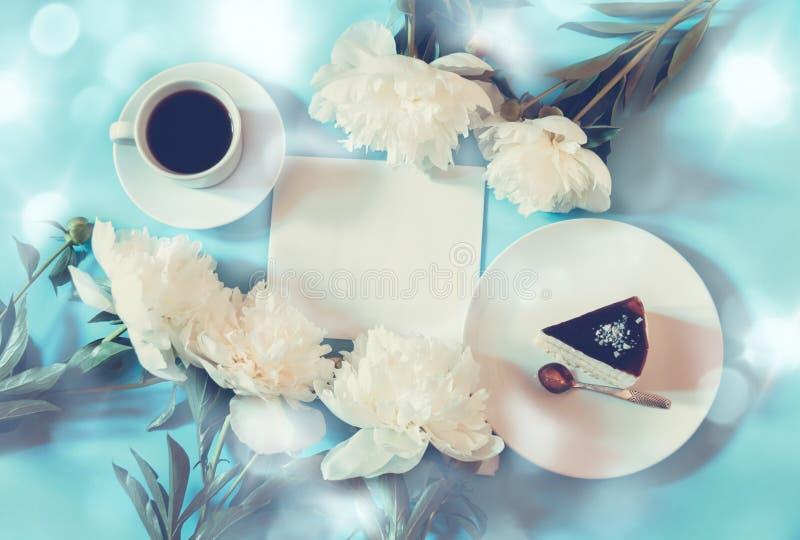咖啡、蛋糕,白色牡丹花和空的卡片您的文本的在蓝色背景 库存图片