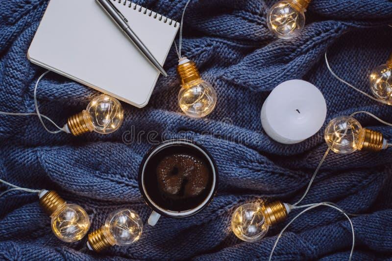 咖啡、蜡烛、笔记本、笔和温暖的毛衣,装饰用被带领的光 免版税库存照片