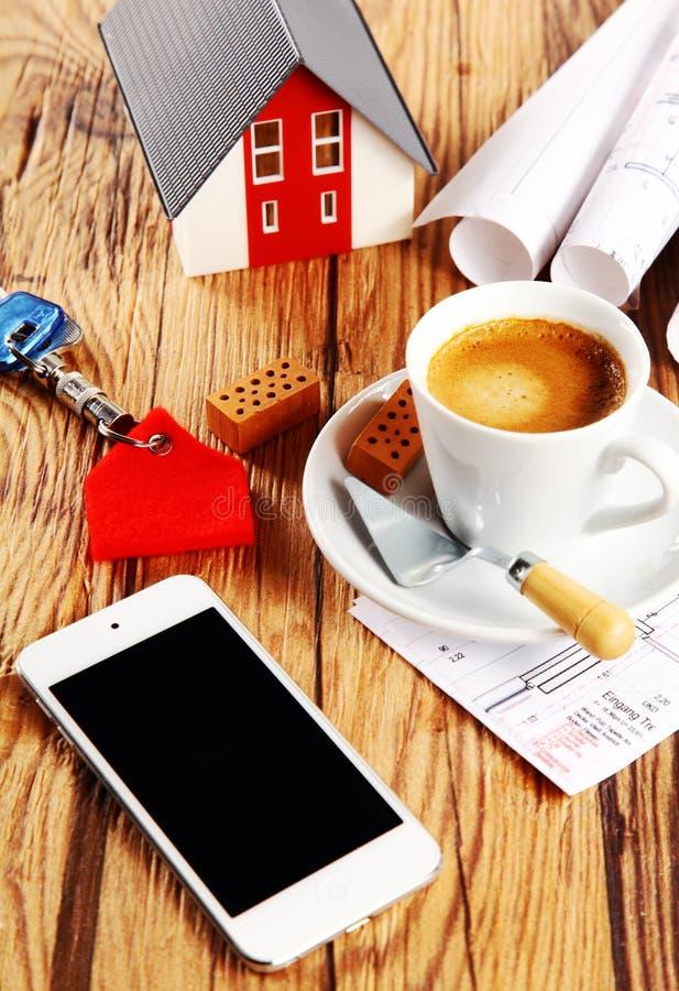 咖啡、议院、剪影和电话在木表上 免版税库存照片