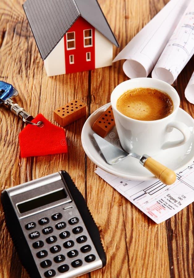 咖啡、议院、图纸和计算器在表上 库存照片