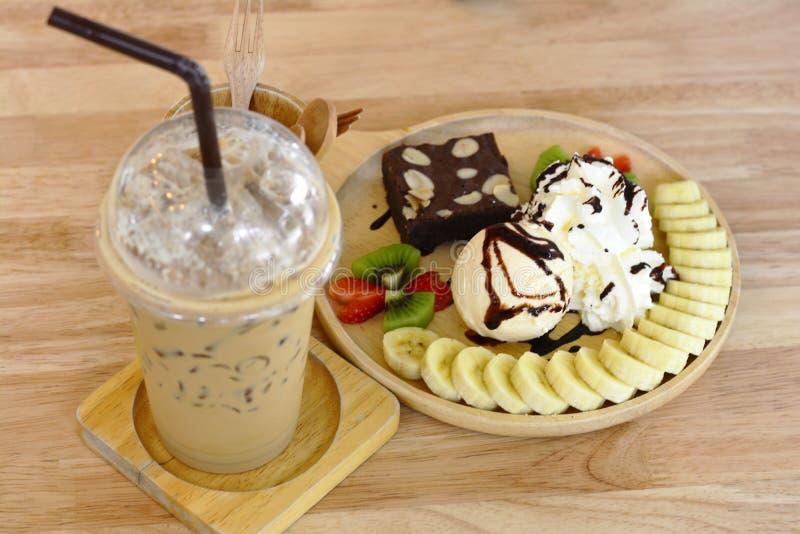 咖啡与冰淇凌的时间点心在木桌背景 免版税库存照片