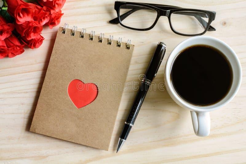 咖啡与花和笔记薄的在木桌上 免版税库存照片