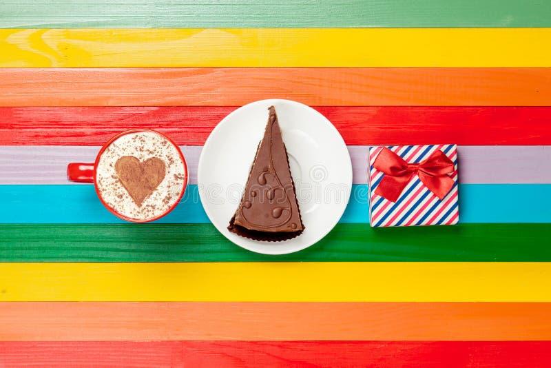 咖啡与蛋糕和礼物盒的热奶咖啡 免版税库存照片