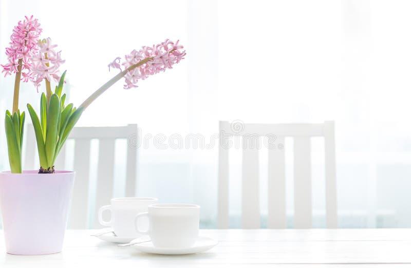 咖啡与风信花的在白色桌上开花 库存图片