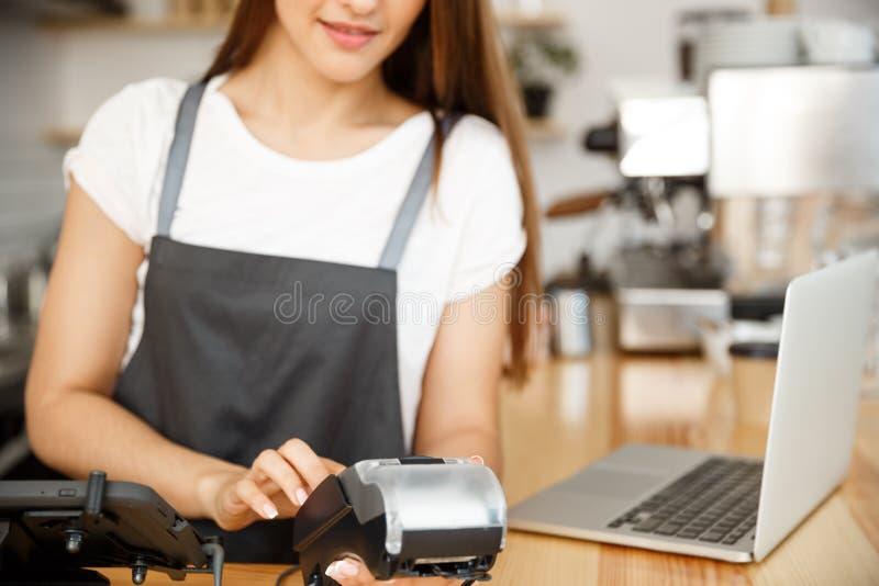 咖啡企业概念-给顾客的美丽的女性barista付款服务有信用卡和微笑的 免版税库存照片