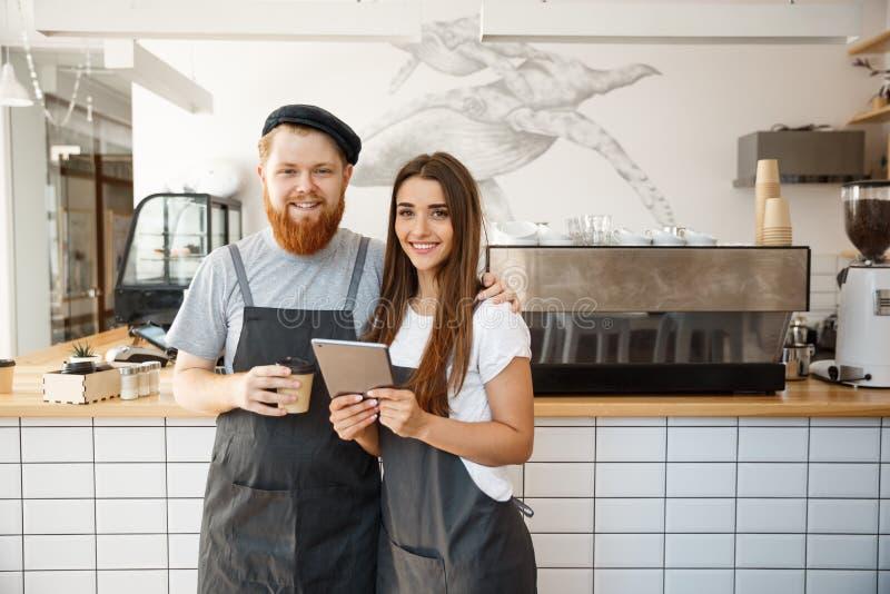 咖啡企业概念-运作和飞行在片剂的小咖啡店愉快的年轻夫妇企业主  库存照片
