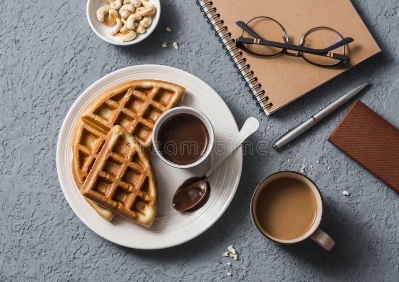 咖啡休息在工作场所 咖啡和维也纳奶蛋烘饼用巧克力汁在灰色背景 库存照片