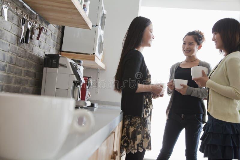 咖啡休息的三名女实业家在办公室 免版税库存照片