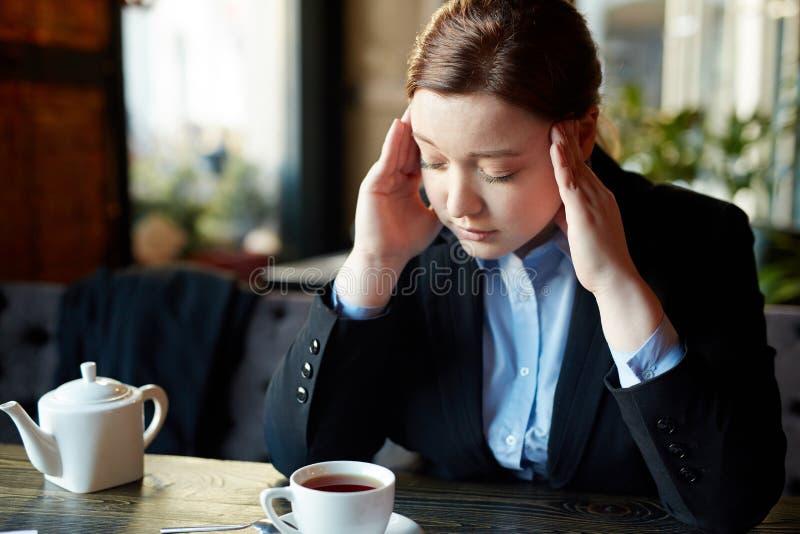 咖啡休息的疲乏的年轻女实业家 库存照片