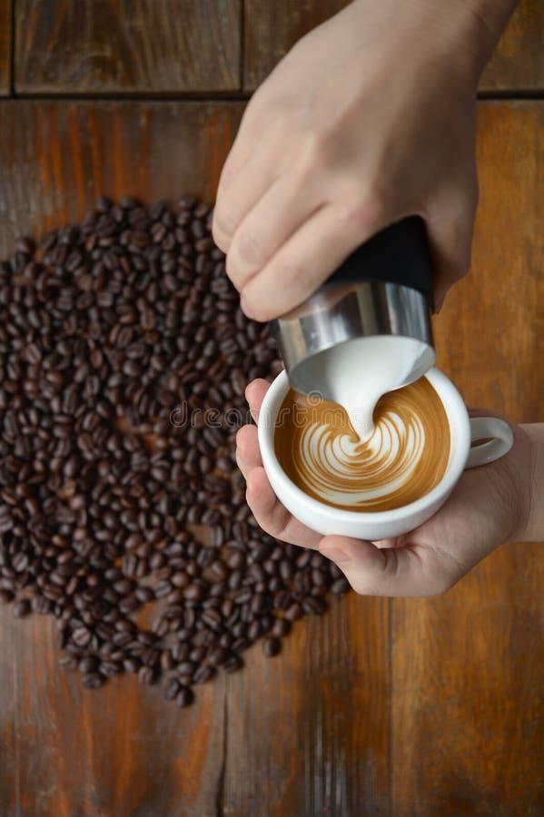 咖啡做由barista的拿铁艺术在老木backgrou 库存图片