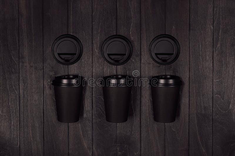 咖啡包装大模型-集合fo三黑纸杯和空白的盖帽在深黑色木板,咖啡馆内部 图库摄影
