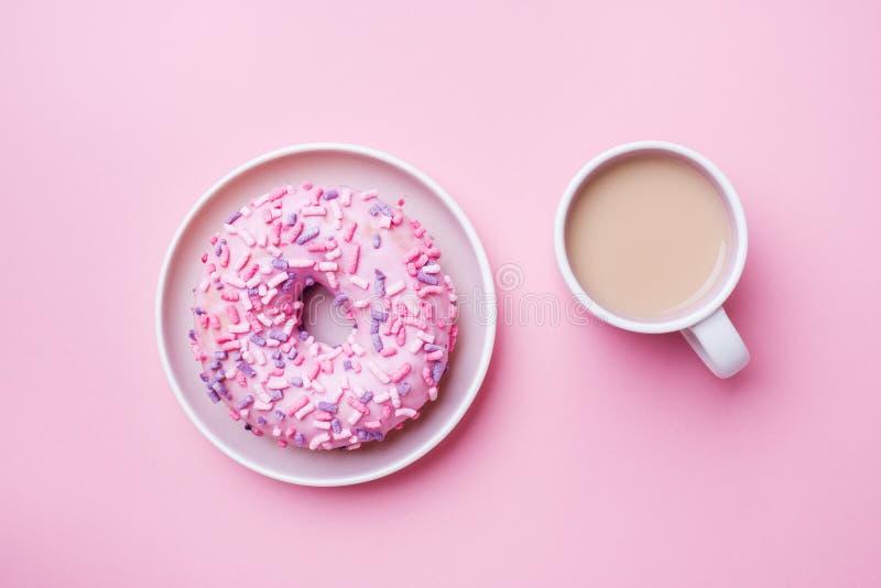咖啡和一个多福饼在桃红色背景 E 免版税图库摄影