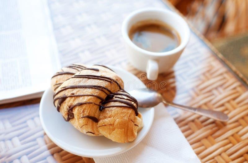 咖啡和一个新月形面包在桌上 免版税库存图片