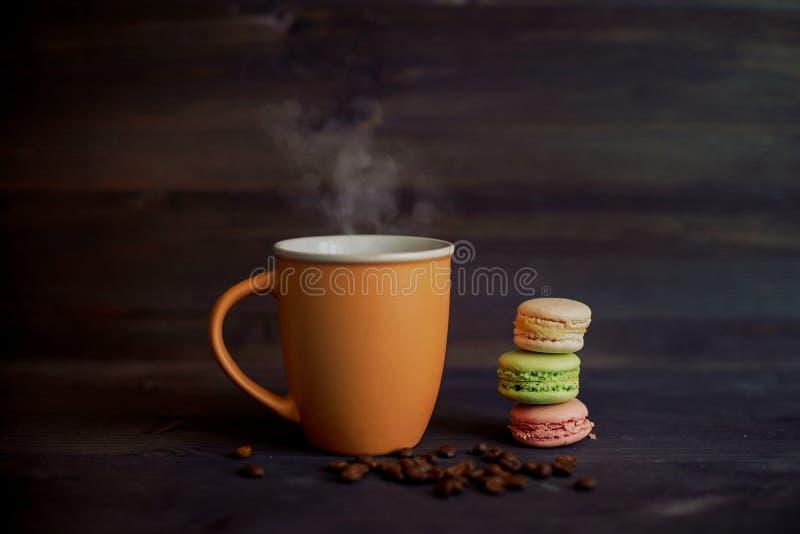 咖啡和五颜六色的蛋白杏仁饼干 免版税库存照片