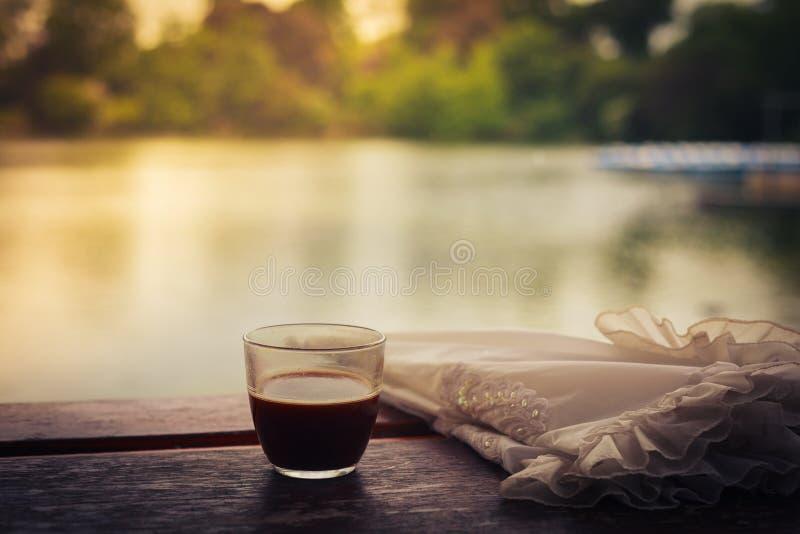 咖啡和伞在桌上由湖 免版税图库摄影
