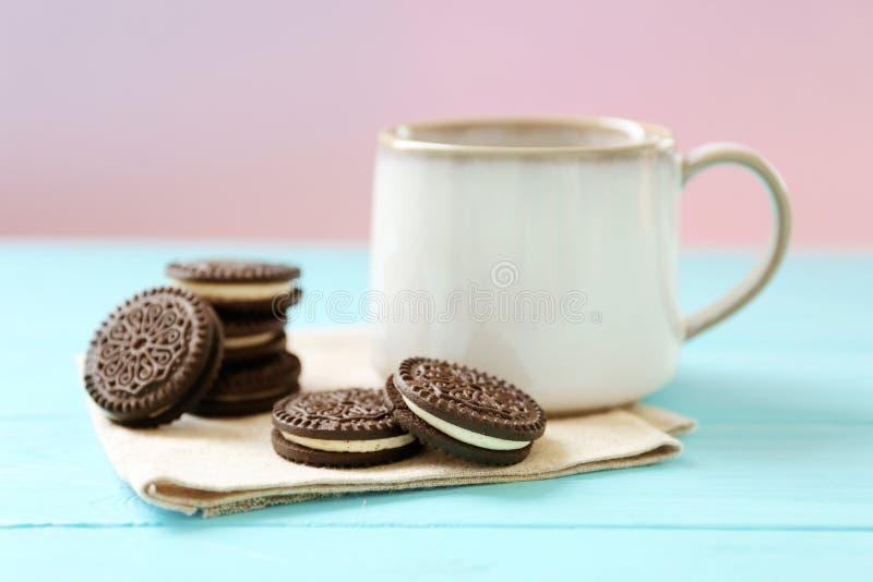 咖啡和可口巧克力曲奇饼在木桌上 免版税图库摄影