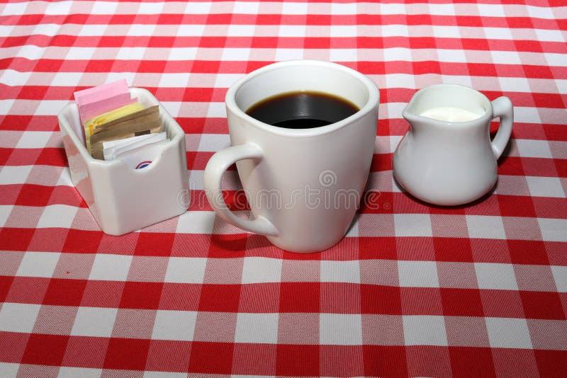 咖啡和奶油在桌布 库存照片
