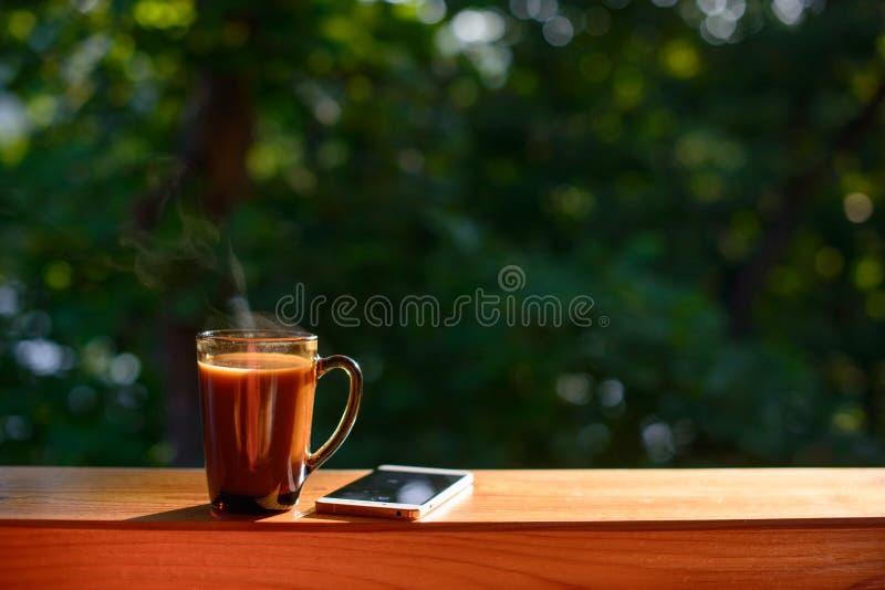 咖啡和手机在窗台在被弄脏的森林背景晴朗的夏日 库存照片