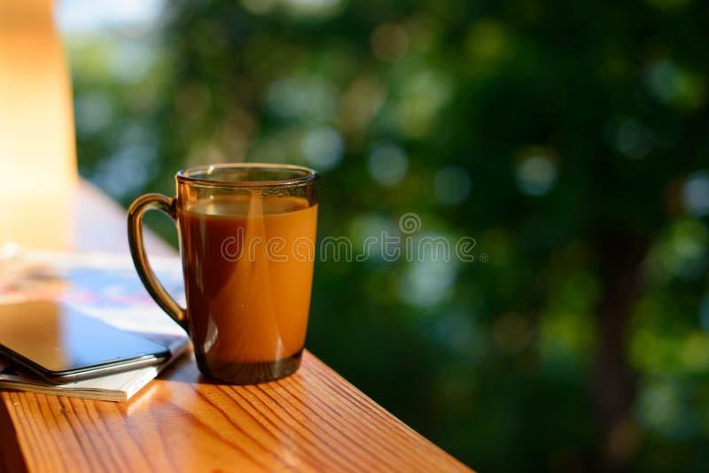 咖啡和手机在窗台在被弄脏的森林背景晴朗的夏日 免版税库存图片