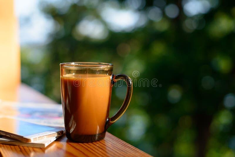 咖啡和手机在窗台在被弄脏的森林背景晴朗的夏日 免版税库存照片