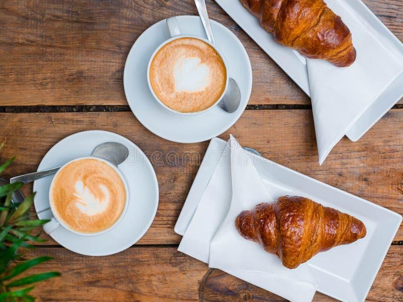 咖啡和新月形面包早餐咖啡馆文化的 与两个小杯子热奶咖啡的新月形面包与图片,顶视图 库存图片