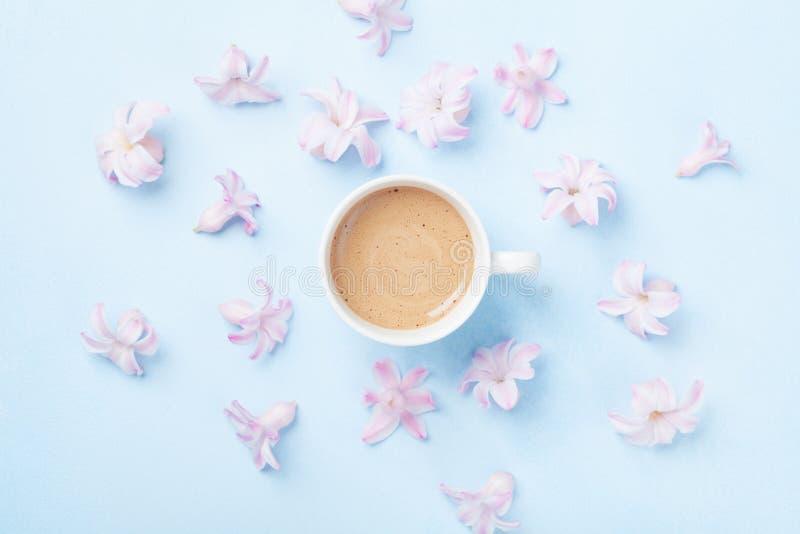 咖啡和桃红色花在蓝色淡色背景顶视图 创造性和时尚构成 平的位置样式 免版税库存图片