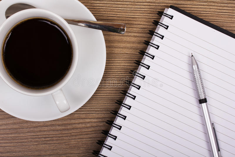 咖啡和笔记本木表面上 库存照片
