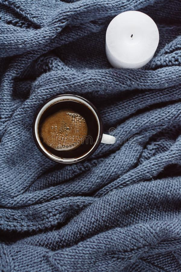咖啡和蜡烛在蓝色被编织的毛线衣 平的位置,顶视图 库存照片