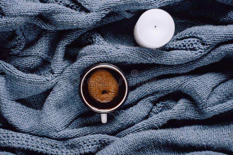 咖啡和蜡烛在蓝色被编织的毛线衣 平的位置,顶视图 免版税库存图片