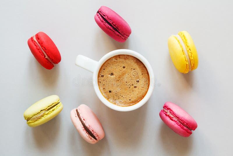 咖啡和被分类的五颜六色的macarons或者蛋白杏仁饼干在灰色背景,顶视图,平的位置 图库摄影