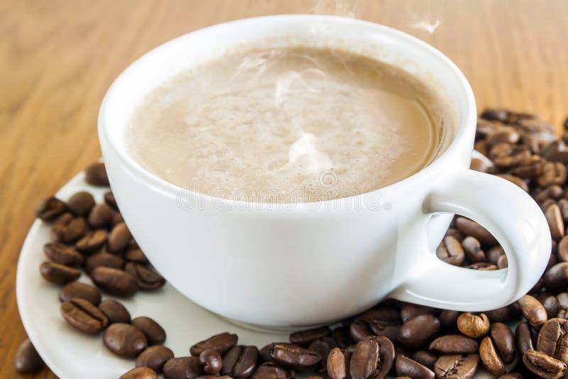 咖啡在一个白色杯子和咖啡豆的在木桌ba 库存图片